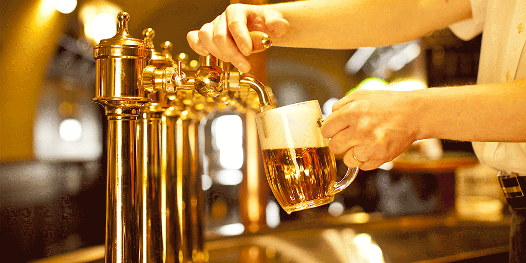a bartender pours a perfect mug of beer with good head