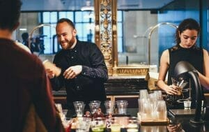 Professional and well trained male female bartenders serving cocktails